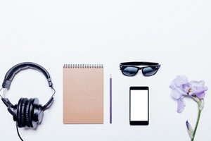 Blue flower, headphones, notebook and mobile phone on a white background, top view