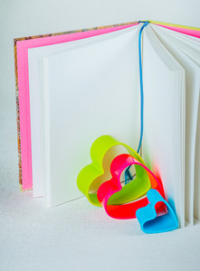Blue red and green hearts inside an open book with bookmark