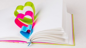 Blue red and green hearts over diary book on white table