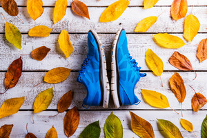 Blue running shoes on white wooden floor. Studio shot on wooden background.