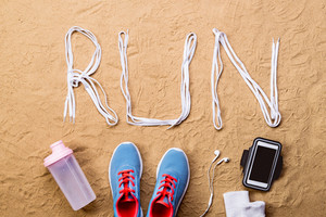 Blue sports shoes with pink shoelaces, water bottle, smart phone, watch, wristbands and big run sign on sand beach background, studio shot, flat lay.