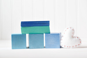 Blue wooden blocks with heart cushion on a white table