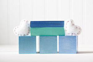 Blue wooden blocks with heart cushions on a white table