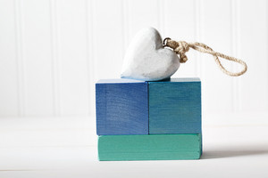 Blue wooden blocks with wooden heart on a white table