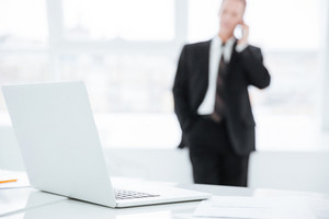 Blur image of business man standing near the window and talking at phone. Focus on table with laptop