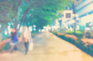 Blurred abstract bokeh background of people walking in the city at night