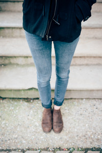 blurred close up legs with jeans of young beautiful hipster sporty blonde woman in town