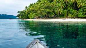 Boat approaching local Village on Friwen Island, West Papuan, Raja Ampat, Indonesia