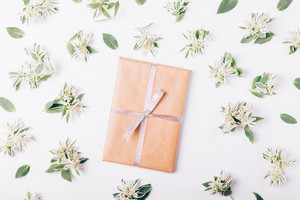 Book in wrapping paper with ribbon among green flowers and leaves on white table top view