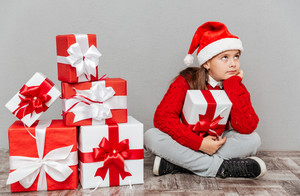 Bored little girl in santa claus hat with gift box sitting and waiting