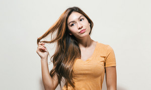 Bored young woman on a off white background