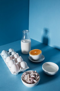 Bottle of milk, eggs, pasta and orange half , over blue background