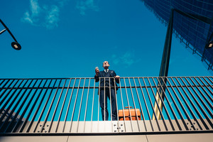 Bottom up perspective of middle-age contemporary businessman leaning on a handrail holding smart phone - work, business, technology concept