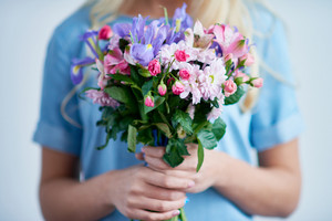 Bouquet of fresh spring flowers held by young female