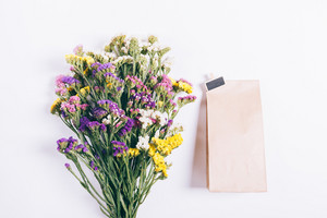 Bouquet of multicolored wildflowers and a package with a gift on a white background