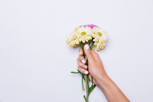 Bouquet of yellow and violet flowers in female hand with white manicure, copy space
