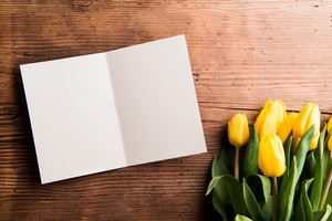 Bouquet of yellow tulips and empty greeting card. Studio shot on wooden background. Copy space, flat lay.