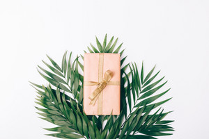 Box with gift and ribbon and palm leaves on white background, top view