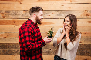 Boy gives girl a gift. wooden background