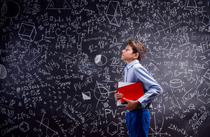 Boy in blue shirt holdin various notebooks against big blackboard with mathematical symbols and formulas