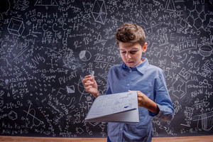 Boy in blue shirt holding notebook and chalk against big blackboard with mathematical symbols and formulas