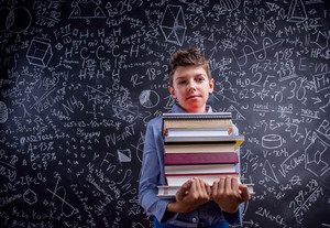 Boy in blue shirt holding various books against big blackboard with mathematical symbols and formulas