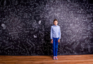 Boy in blue t-shirt against big blackboard with mathematical symbols and formulas
