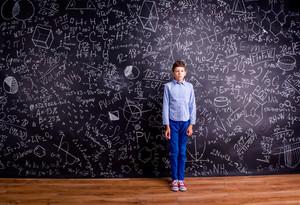 Boy in blue t-shirt against big blackboard with mathematical symbols and formulas