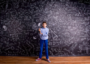 Boy in blue t-shirt, holding a piece of chalk, against big blackboard with mathematical symbols and formulas