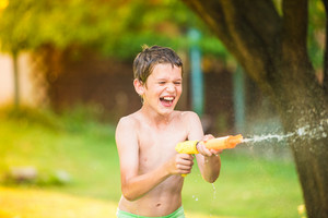 Boy splashing children with water gun, fun in garden, sunny summer day, back yard