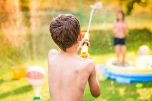 Boy splashing girl with water gun in garden swimming pool, sunny summer day, back yard, rear view