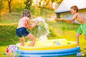 Boy splashing girl with water gun in garden swimming pool, sunny summer day, back yard