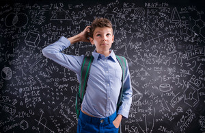 Boy  thinking, scratching his head against big blackboard with mathematical symbols