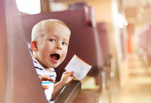 Boy travelling in retro train. He is holding train ticket.