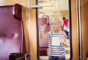 Boy travelling in retro train. He is sticking to glass, making funny faces.