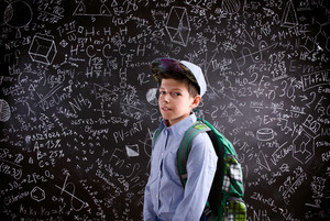 Boy  with schoolbag against big blackboard with mathematical symbols and formulas