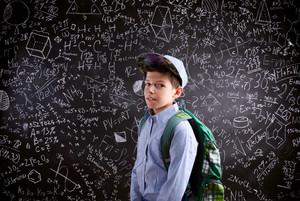 Boy  with schoolbag against big blackboard with mathematical symbols and formulas