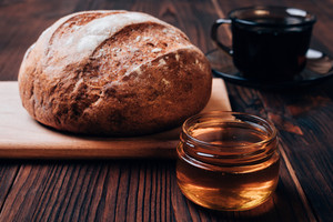 Bread, cup of tea and honey on a brown table, close-up