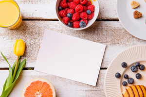 Breakfast meal. Empty piece of paper. Studio shot on white wooden background. Flat lay, copy space.