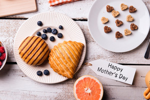 Breakfast with Happy Mothers Day tag. Studio shot on wooden background.