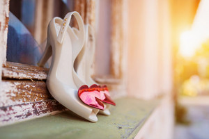 Bridal shoes with red hearts laid on window parapet