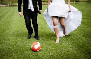 Bride and groom are playing at the football pitch