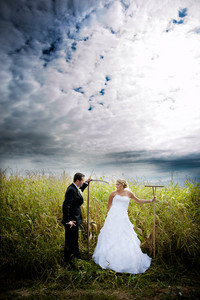 Bride and groom are posing outdoors