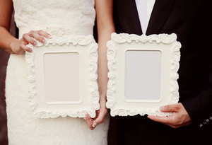 Bride and groom holding vintage photo frames, cut out