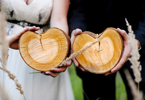 Bride and groom holding wooden hearts in nature