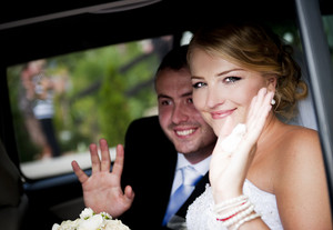 Bride and groom in the car at the wedding day
