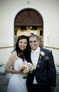 Bride and groom posing in front of the church