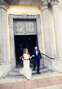 Bride and groom walking out of the church holding hands