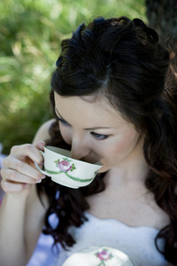 Bride in white wedding dress drinking coffee at the meadow