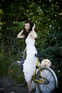 Bride in white wedding dress on retro bicycle